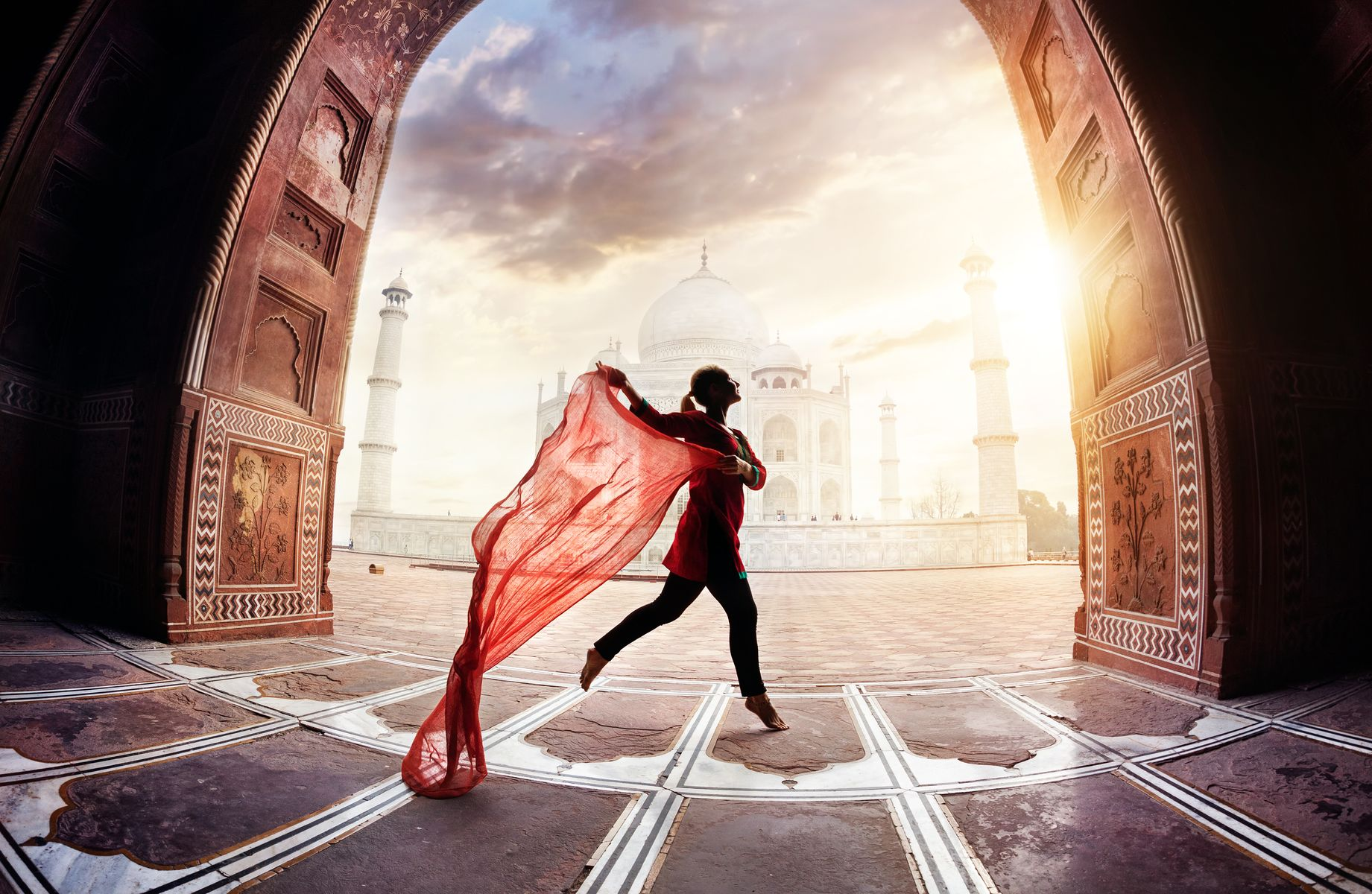 Mujer con bufanda roja bailando cerca del Taj Mahal en Agra, Uttar Pradesh, India