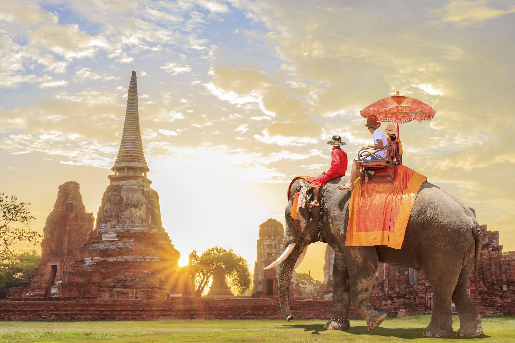 Turistas en un paseo por elefante en la ciudad antigua con el amanecer de fondo, Camboya